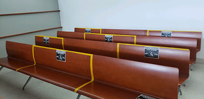 Photo of Bronx Hall of Justice courtroom benches marked to ensure social distancing