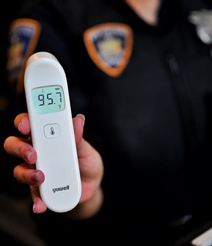 Court Officer uses thermometer to check person's temperature